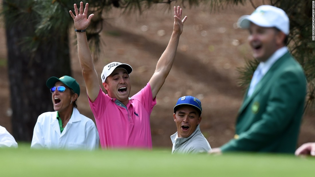 U.S. golfer Justin Thomas (C) celebrates with Rickie Fowler after shooting a hole-in-one at the fourth...