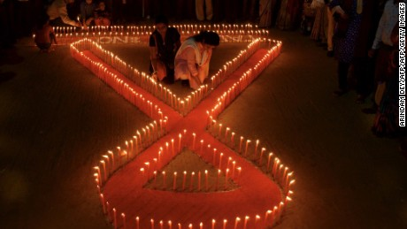 Indian NGO volunteers light candles in the shape of a ribbon during an awareness rally on the eve of World Aids Day in Agartala, the capital of northeastern state of Tripura on November 30, 2015. / AFP / ARINDAM DEY        (Photo credit should read ARINDAM DEY/AFP/Getty Images)