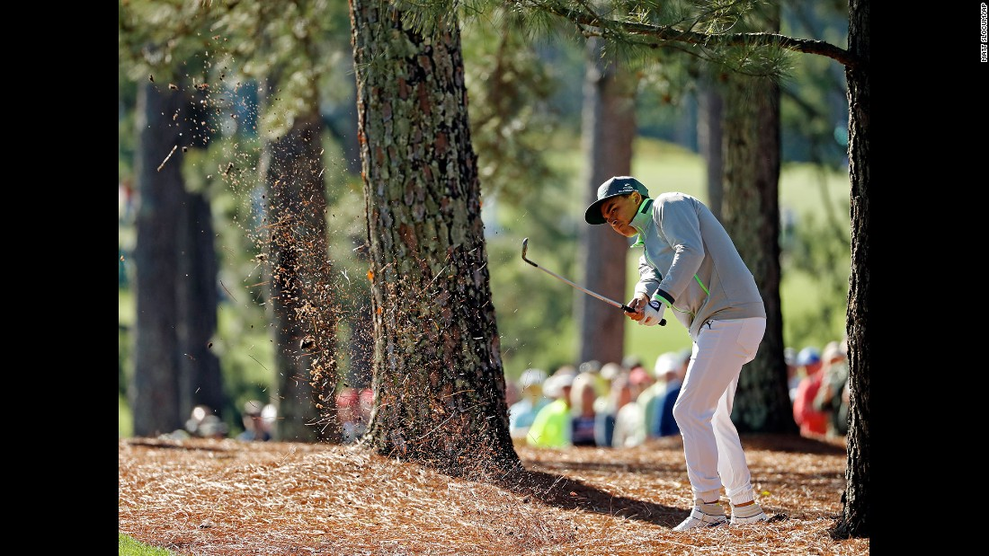Rickie Fowler hits out of the trees near the first fairway.