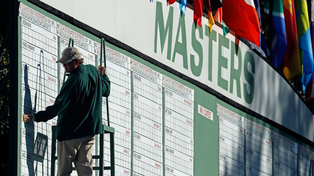 A scorekeeper places numbers on the leaderboard during the first round.