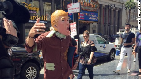 "A Trump look-alike seeks cash tips in exchange for posing with tourists because ""this Donald is broke."""