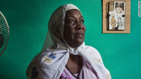 Elsa Morales, a Cuban woman now known with the Muslim name of Fatima, seen in her bedroom, with a Jesus Christ image in the background. Elsa is the only Muslim member of her family.