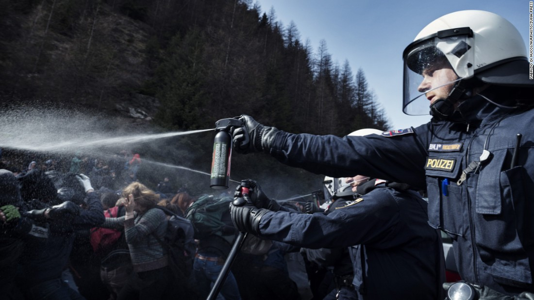 An Austrian police officer uses pepper spray to ward off protesters after violence broke out at a pro-immigration rally near the Italian border on Sunday, April 3.