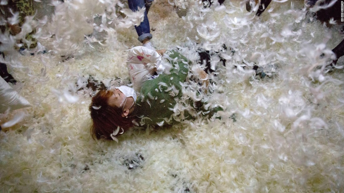 "A pillow-fight participant falls to a floor covered with feathers Saturday, April 2, in Beijing. It was<a href=""http://pillowfightday.com"" target=""_blank""> International Pillow Fight Day,</a> and similar events were held across the world."