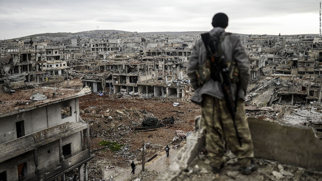 "A Kurdish marksman stands atop a building as he looks at the destroyed Syrian town of Kobani on January 30, 2015. After four months of fighting, Peshmerga forces <a href=""http://www.cnn.com/2015/02/04/middleeast/kobani-syria-destruction/index.html"" target=""_blank"">liberated the city</a> from the grip of ISIS."