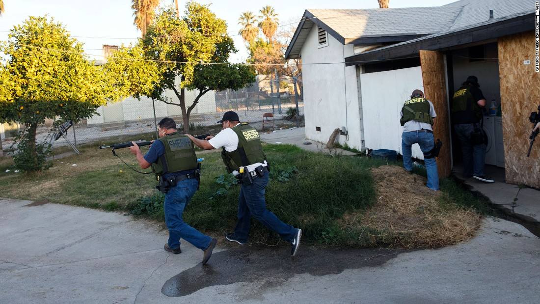 "Law enforcement officers search a residential area in San Bernardino, California, after a <a href=""http://www.cnn.com/2015/12/02/us/gallery/san-bernardino-shooting/index.html"" target=""_blank"">mass shooting</a> killed at least 14 people and injured 21 on December 2, 2015. <a href=""http://www.cnn.com/2015/12/03/us/san-bernardino-shooting/index.html"" target=""_blank"">The shooters</a> -- Syed Rizwan Farook and his wife, Tashfeen Malik -- were fatally shot in a gunbattle with police hours after the initial incident. The couple supported ISIS and had been planning the attack for some time, investigators said."