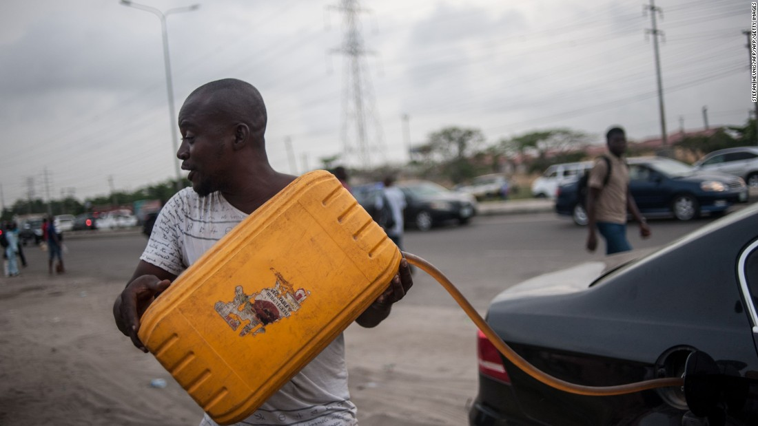 Due to the fuel shortage, there has been increased activity of black market hawkers selling gas at inflated prices. Pictured, a hawker fills a car with fuel on the side of the road in Lagos on April 6, 2016.