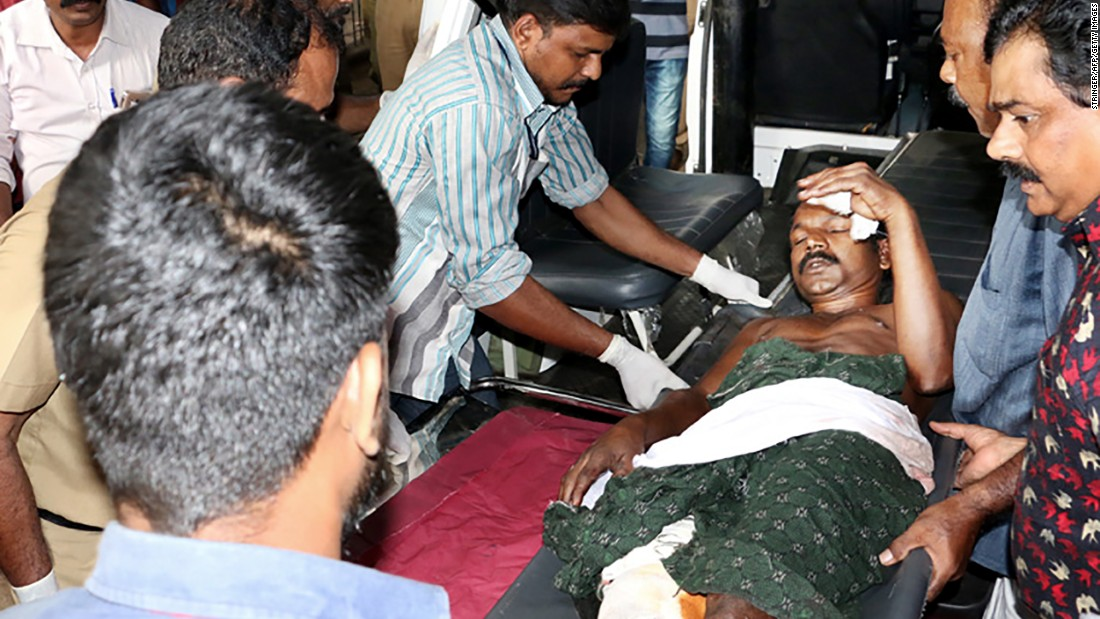 Indian medical officials and bystanders carry an injured man from a vehicle into a hospital in Paravur, India.