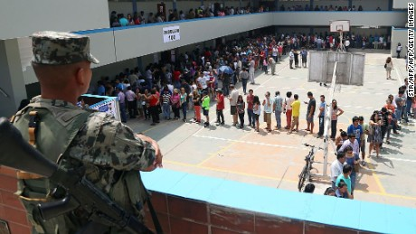 An Army soldier stands guard as hundreds of citizens queue up to vote at a polling station during the presidential elections in Lima on April 10, 2016.  Peruvians voted Sunday on whether Keiko Fujimori, daughter of an ex-president jailed for massacres, should become their first female leader in an election marred by alleged vote-buying and deadly attacks. / AFP / STR        (Photo credit should read STR/AFP/Getty Images)