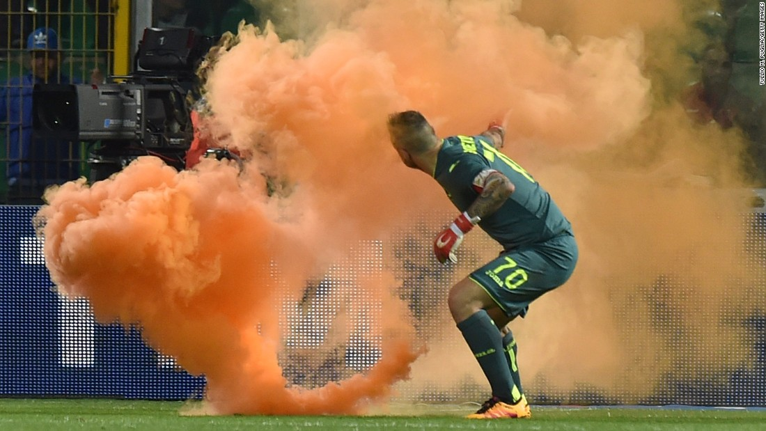 "A flare is thrown onto the field near Palermo goalkeeper Stefano Sorrentino during an Italian league match in Palermo on Sunday, April 10. The match was stopped twice because of crowd trouble, <a href=""http://www.bbc.com/sport/football/36011691"" target=""_blank"">according to the BBC.</a>"