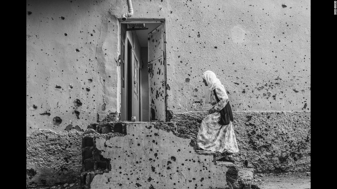 A woman waits outside her house in Diyarbakir, Turkey, in October. The wall was riddled with bullet marks during clashes between Turkish armed forces and Kurdish rebels.