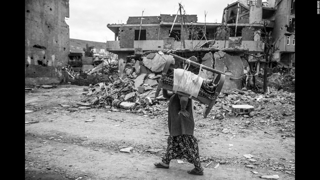 "A woman carries her baby in the ruins of Cizre, Turkey, in March. ""What I witnessed there was unforgettable,"" photographer Emin Ozmen said. ""I was really shocked to see this kind of scene in my country: 40% of the city was totally destroyed during the clashes."""
