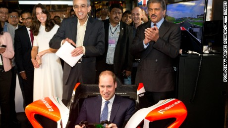 Prince William flies in a Formula E simulator in India, watched by his wife Catherine, Duchess of Cambridge.