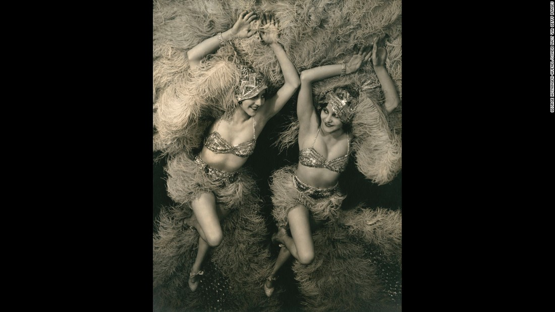 Actresses Beth and Betty Dodge wear matching stage costumes as they take a publicity portrait in 1929. The twins wore sequined caps, tops and bloomers to go with ostrich-feather skirts and fans.