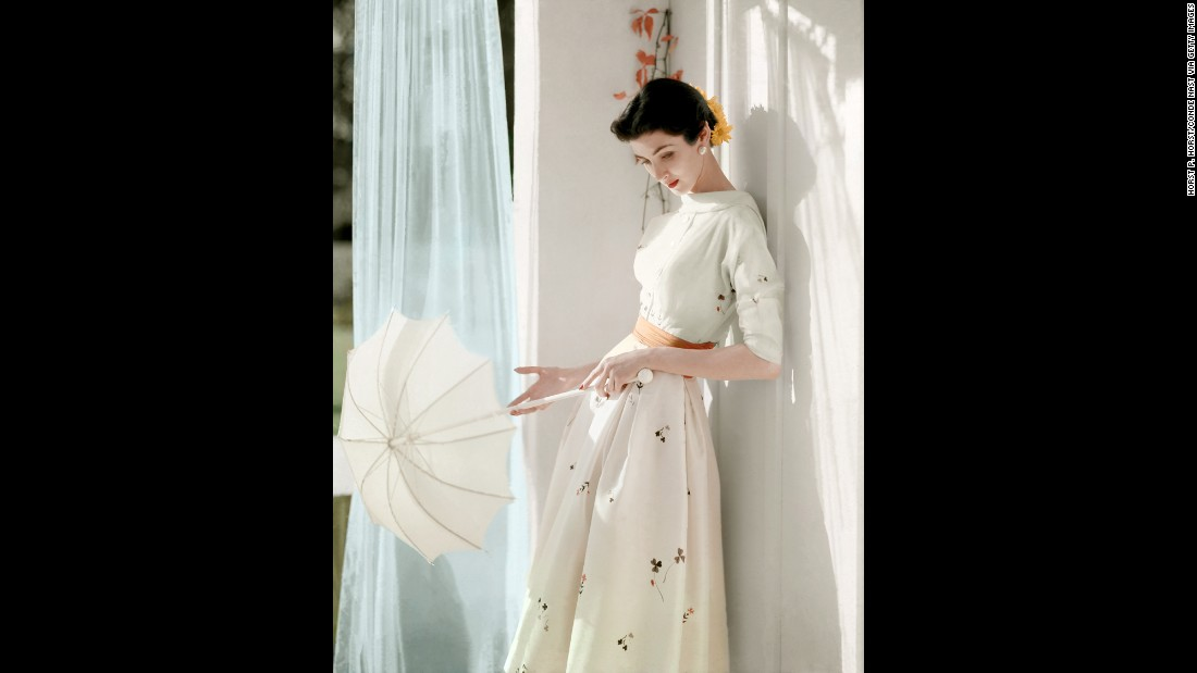 A model holds a parasol in her hands as she leans against a wall in 1953.