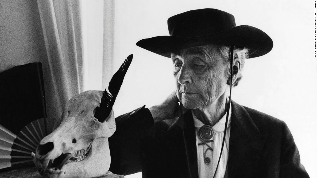 In 1967, artist Georgia O'Keeffe examines an animal skull with a black feather in one of its eye sockets.