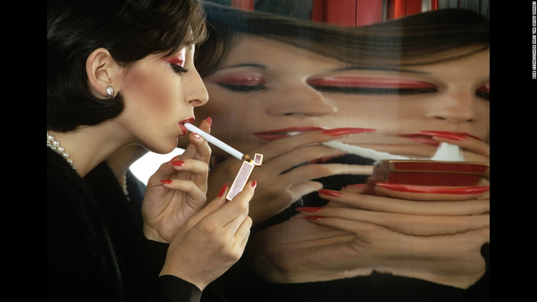 Model and actress Anjelica Huston lights a cigarette in front of a large mirror in 1972. This is one of more than 30,000 unseen photos released by Conde Nast, the magazine house behind Vogue, GQ and Vanity Fair.
