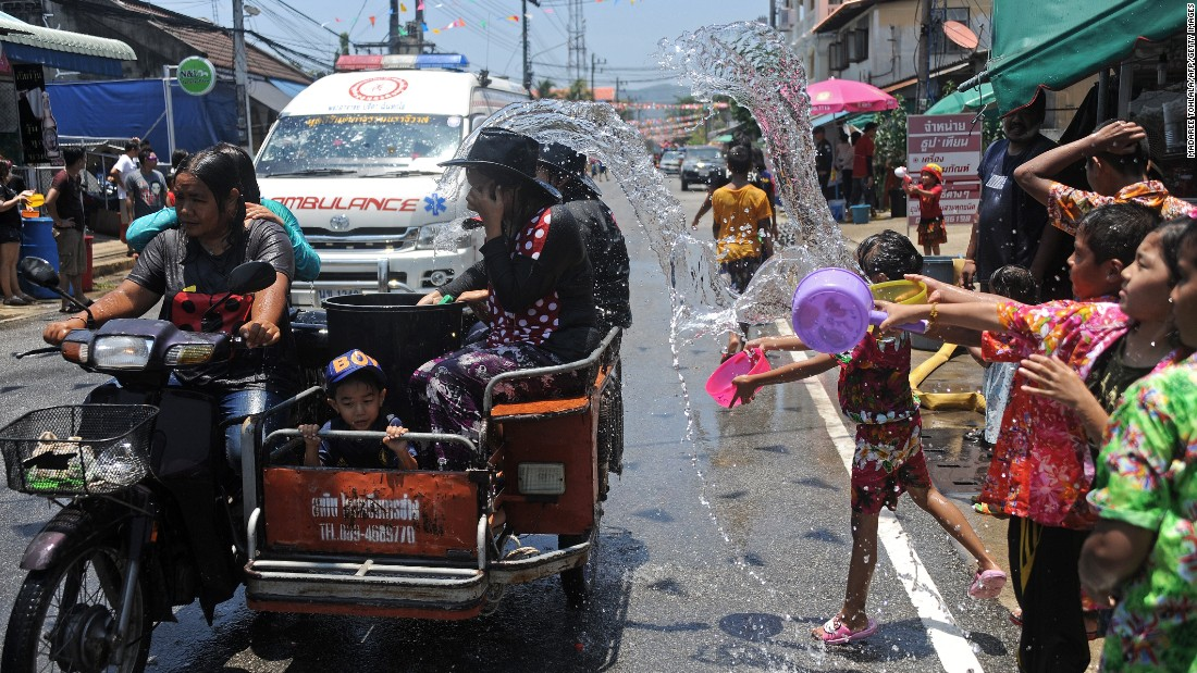 Locals splash water on road travelers in Narathiwat to kick off the three-day Songkran festival. On the first day, many families and friends celebrate by visiting temples and pouring water on each others' hands as a blessing.