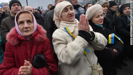 "Elderly women pray during a rally on Independence Square in Kiev on February 21, 2016. Protesters of the Radical Right Power organization pitched tents on the square and declared the ""Third Maidan"", demanding the resignation of Ukrainian President Petro Poroshenko and his governmant. / AFP / SERGEI SUPINSKY        (Photo credit should read SERGEI SUPINSKY/AFP/Getty Images)"