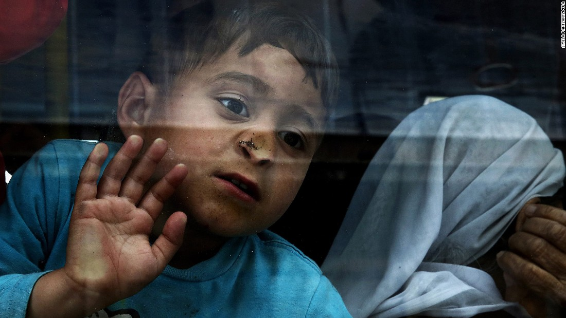 "A boy looks out of a bus window as migrants from Syria and Iraq are transferred to a facility in Skaramagas, Greece, on Monday, April 11. <a href=""http://www.cnn.com/2015/09/03/world/gallery/europes-refugee-crisis/index.html"" target=""_blank"">See Europe's migration crisis in 25 photos</a>"