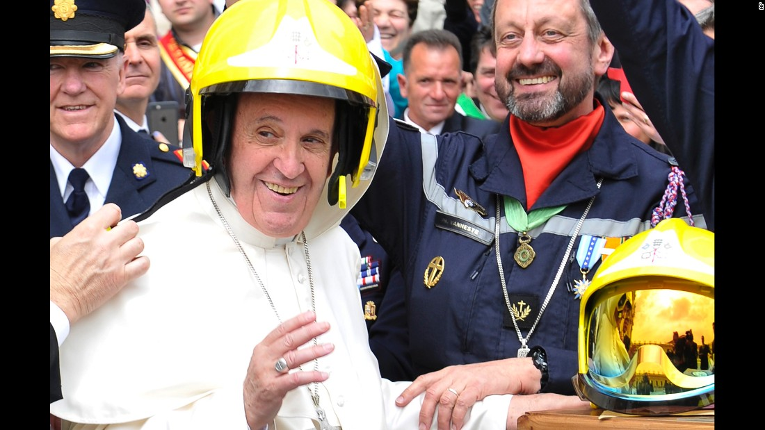 Pope Francis wears a firefighter's helmet as he meets with Vatican firefighters on Wednesday, April 13.