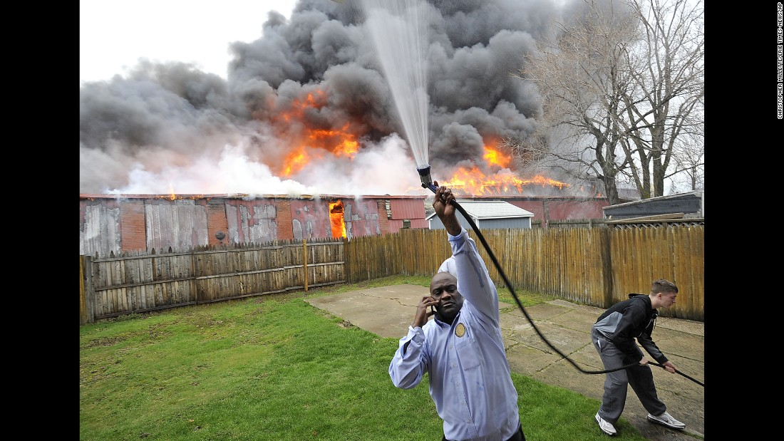 A man in Erie, Pennsylvania, uses a garden hose to wet the side of his house as a warehouse fire rages behind him on Monday, April 11.