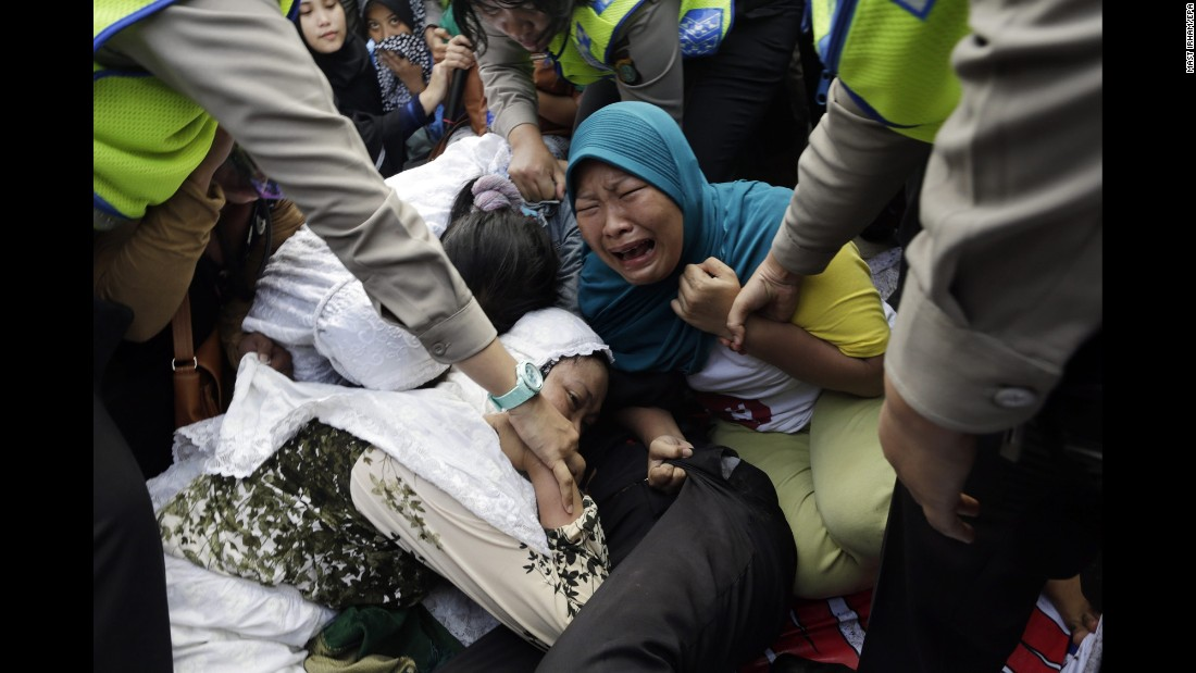 Security officers pull up protesting residents as houses were demolished in a slum area of Jakarta, Indonesia, on Monday, April 11. The government said the homes were illegally built in an area intended for commercial use. Hundreds of families accepted government terms to be moved to low-income housing.