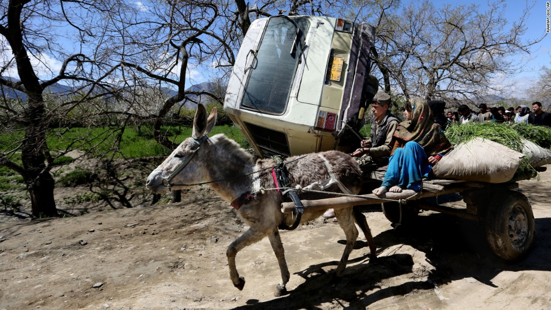 Children in Kabul, Afghanistan, ride a donkey cart past the site of a roadside bomb explosion on Monday, April 11. An Afghan official said at least one person was killed when a bomb ripped through a bus carrying employees of the Education Ministry.