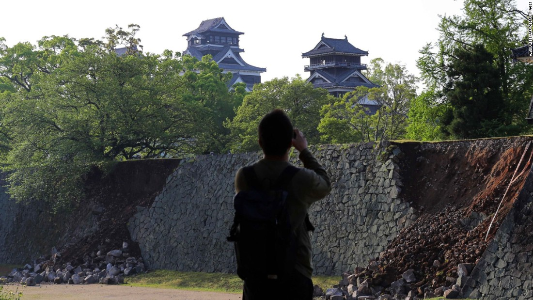 A man takes a picture of a damaged stone wall at Kumamoto Castle, in the city of Kumamoto, on April 15.