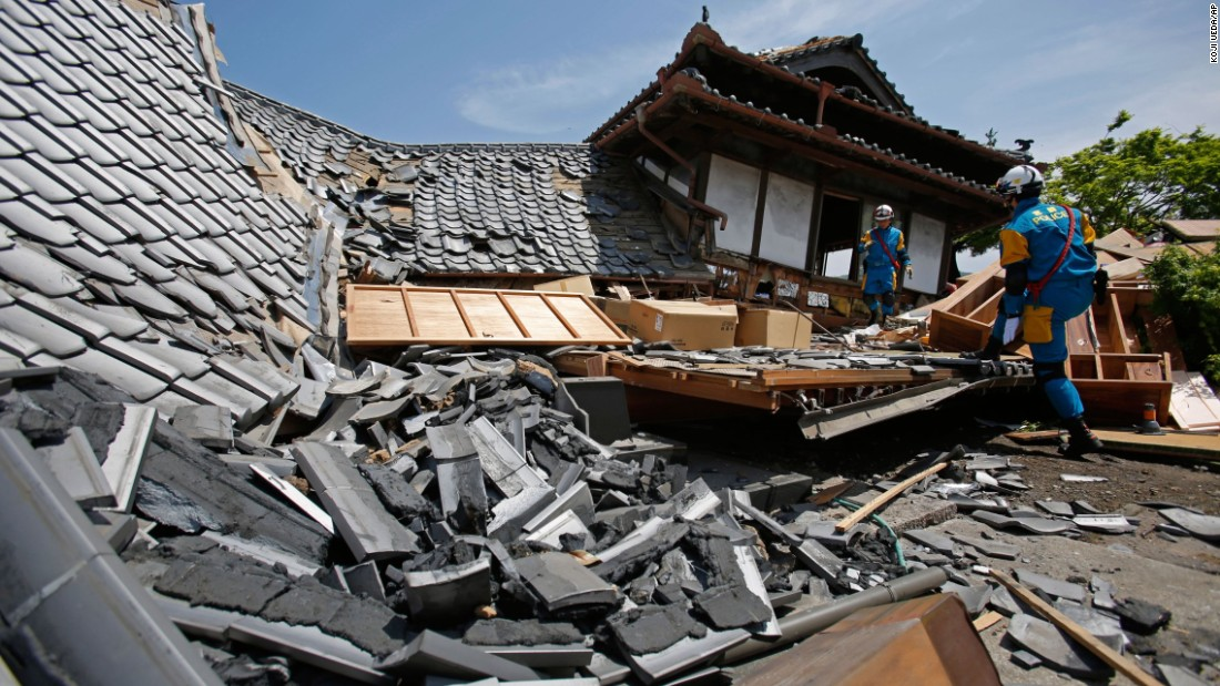 A police rescue team searches a damaged house for earthquake survivors Friday, April 15, in Mashiki, Japan.