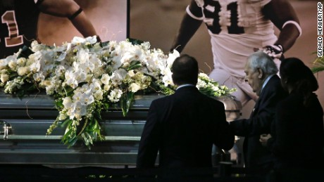 New Orleans Saints owner Tom Benson, right, stands in front of Will Smith's casket.