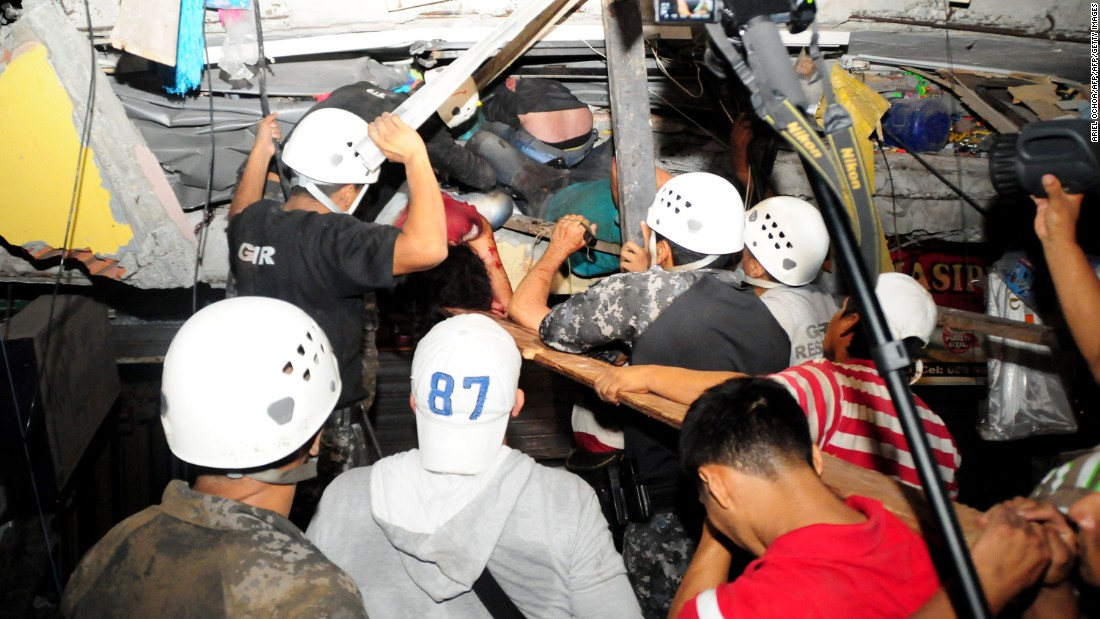 Rescue workers try to pull out survivors trapped in a collapsed building in Manta on April 17.