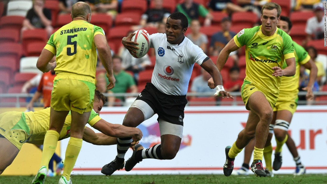 Fiji's Kitione Taliga (C) runs past Australian players during their Cup quarter-final match at the Singapore Sevens rugby tournament on April 17, 2016.