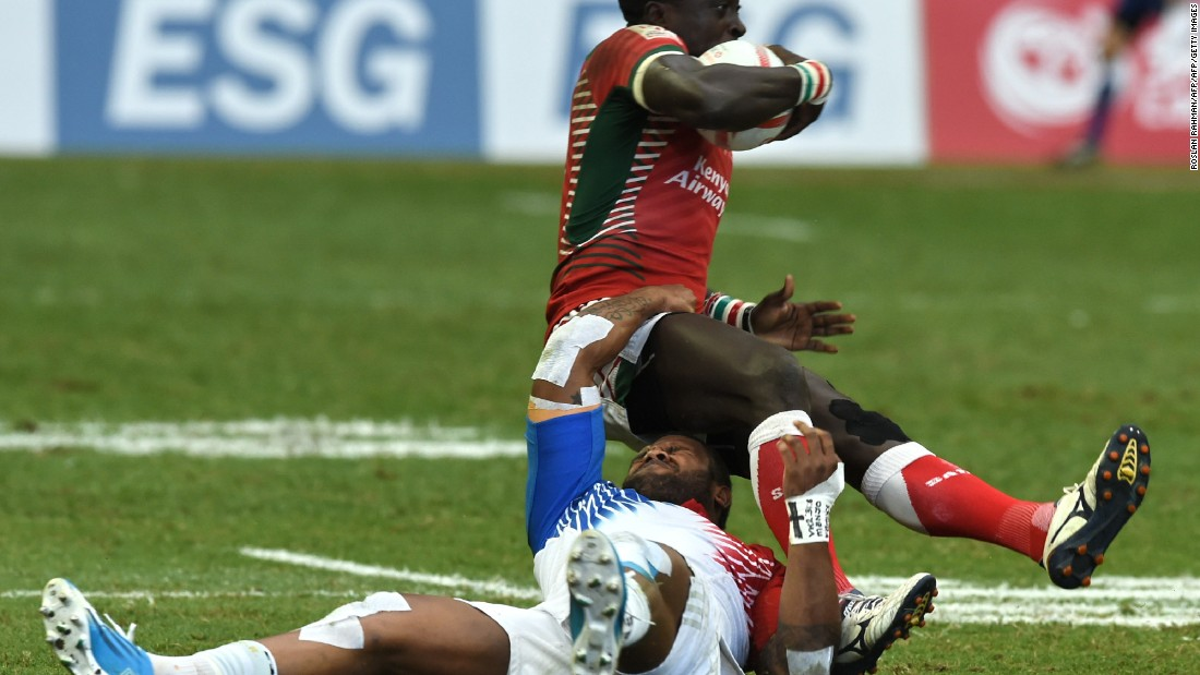 France's Virimi Vakatawa (bottom) tackles Kenya's Collins Injera (top) during their cup quarter-final match at the Singapore Sevens rugby tournament on April 17, 2016.
