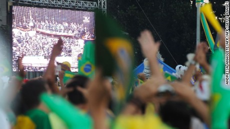 Activists supporting the impeachment of Brazilian President Dilma Rousseff follow on big screens as lawmakers vote on whether the impeachment of Rousseff will move forward, in Brasilia, on April 17, 2016. Thousands of rival protesters gathered Sunday outside Brazil's Congress for a vote on President Dilma Rousseff's political future, waving flags, wearing opposing colors and separated by a wall. Rousseff, whose approval rating has plunged to a dismal 10 percent, faces charges of embellishing public accounts to mask the budget deficit during her 2014 reelection. / AFP / ANDRESSA ANHOLETE        (Photo credit should read ANDRESSA ANHOLETE/AFP/Getty Images)