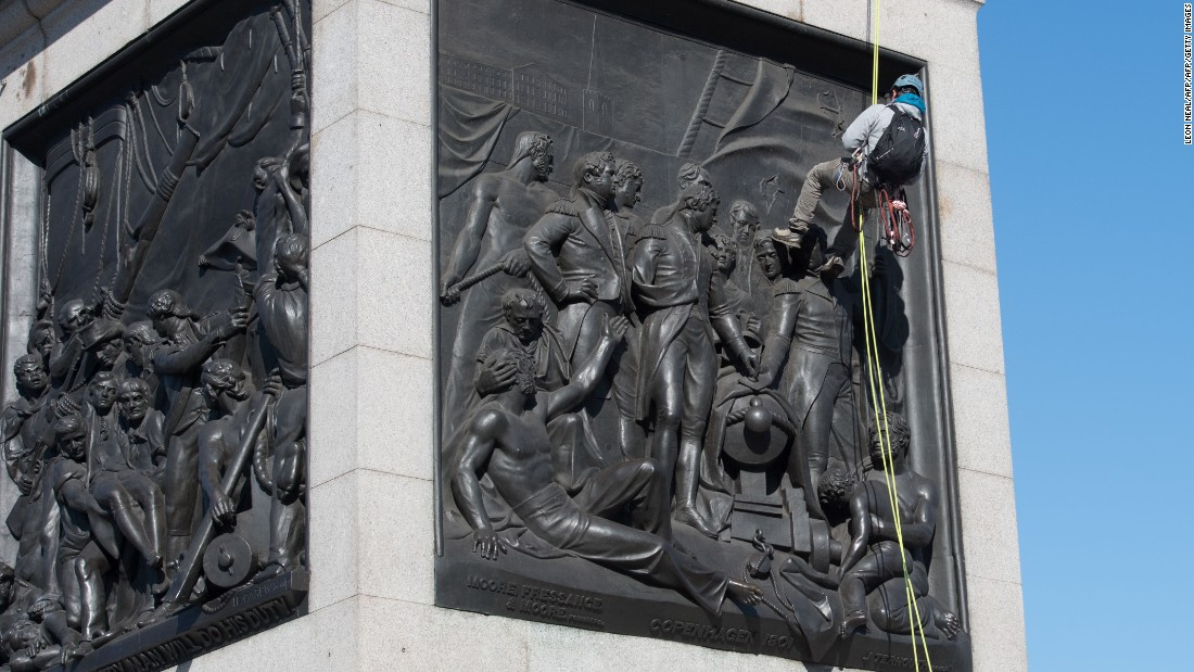 A Greenpeace activist abseils down Nelson's Column statue in Trafalgar Square, central London, after attaching a breathing mask to it on April 18, 2016.
