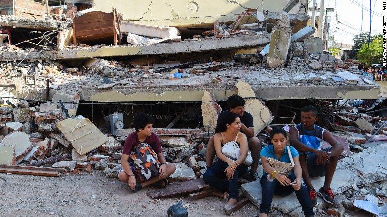 People rest in front of a destroyed house in Manta, Ecuador, on April 17, 2016 a day after a powerful 7.8-magnitude quake hit the country.