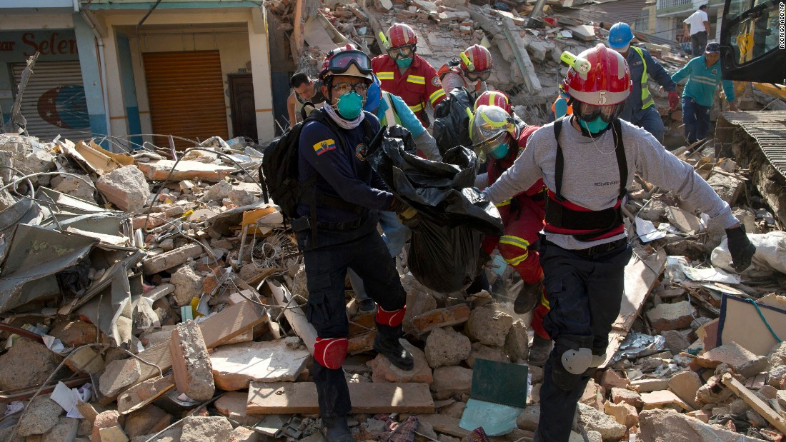 Firefighters remove a body from a destroyed building in Portoviejo on Monday, April 18.