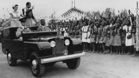 Queen Elizabeth II and Prince Philip wave from an open Land Rover in Ibadan, Nigeria, 1956.