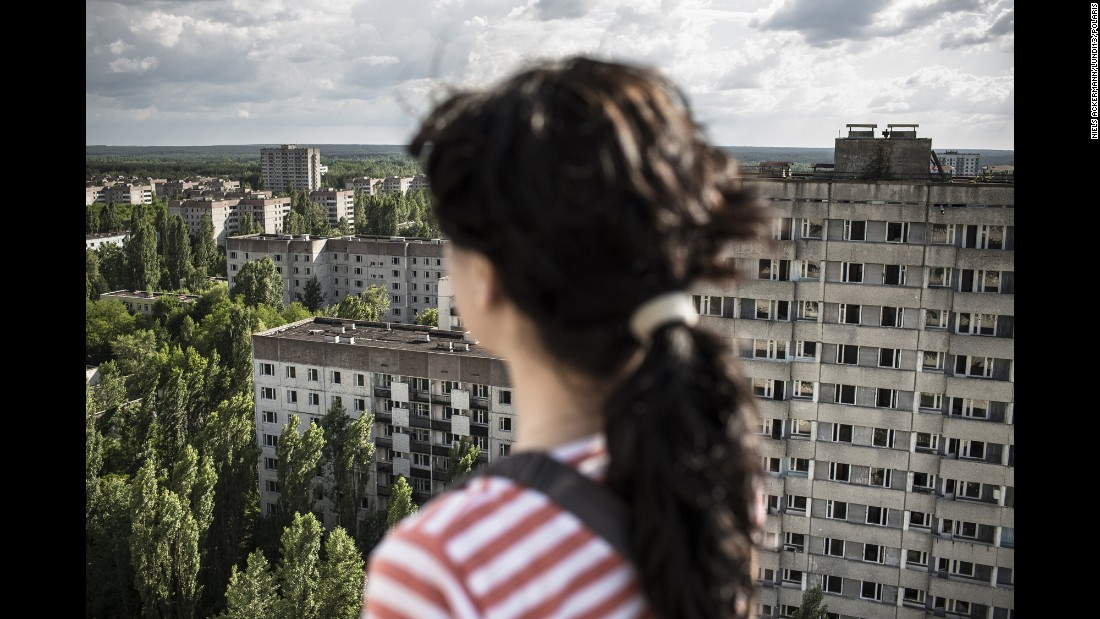 A young woman looks out at the ghost town of Pripyat.