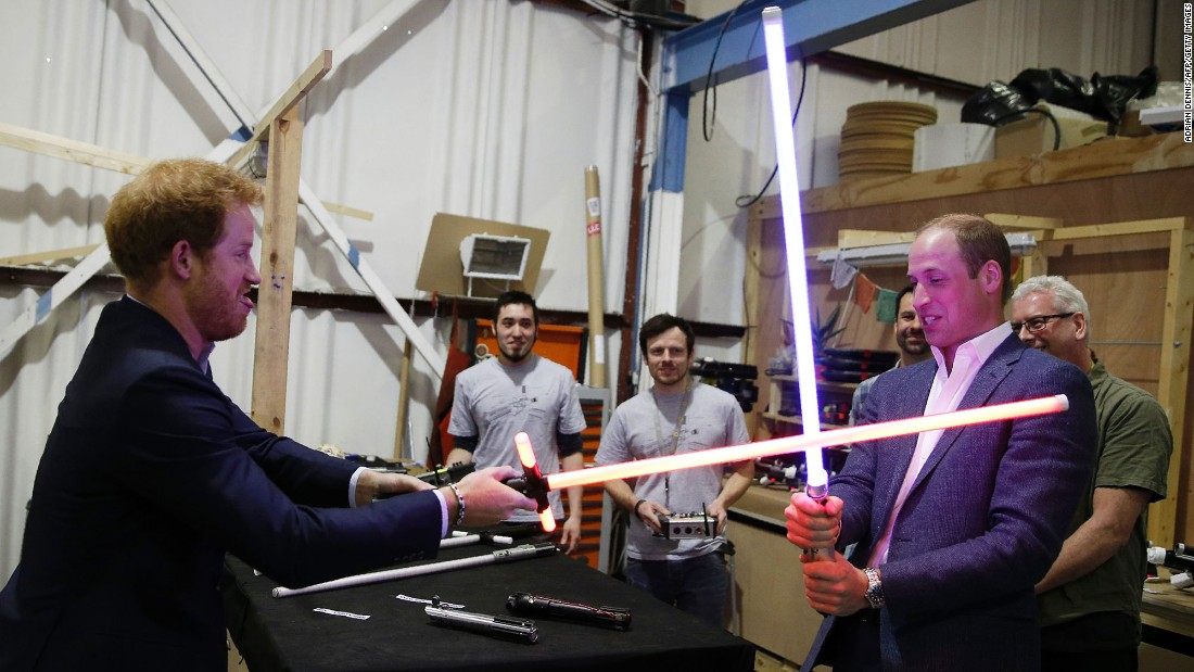 Britain's Prince Harry and Prince William, Duke of Cambridge, try out light sabers during a tour of the Star Wars set at Pinewood Studios outside of London on Tuesday, April 19.