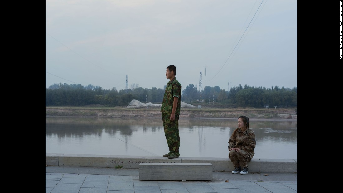 A boy stands near teacher Zhang Dan Dan during training at the Yellow River.
