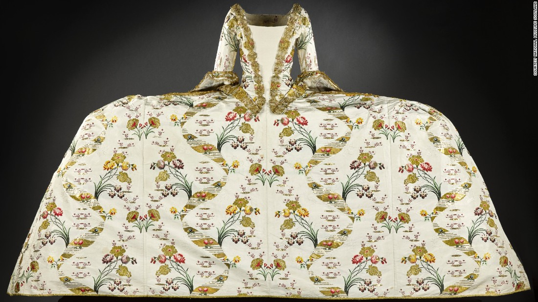 The mantua was worn for court occasions and was designed to be a luxurious garment, often decorated with opulent embroidery incorporating gold or silver thread, to display status and wealth. This example, brocaded in gold and trimmed with gilt lace, is thought to have belonged to the Countess of Haddington. <br /><br />It is particularly interesting to the contemporary eye not only for its extravagance -- the fabric alone would cost the equivalent of around £5,000 ($7,200) today -- but for its sheer enormity.