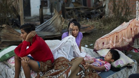 A family wakes up after sleeping outside their collapsed home which was destroyed by the earthquake in Manta, Ecuador April 19.