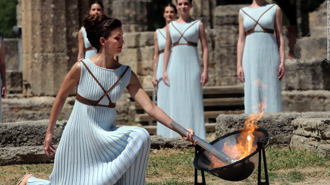 The flame is lit at the Ancient Stadium in Olympia, Greece, and initially derived from the sun's rays in a parabolic mirror. After an elaborate ceremony, it is handed over to the first torchbearer.