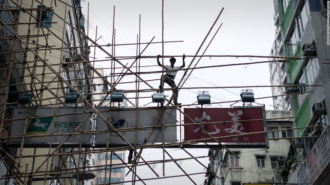 A worker balances on a bamboo scaffolding above the streets in Hong Kong, where bamboo scaffolding remains a common sight many levels above the city streets.