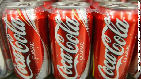 SAN FRANCISCO - JANUARY 16:  Cans of Coca-Cola are seen on the shelf at Tower Market January 16, 2004 in San Francisco, California. Coca-Cola is being investigated by U.S. regulators over allegations raised by a former employee that it had inflated its earnings.  (Photo by Justin Sullivan/Getty Images)