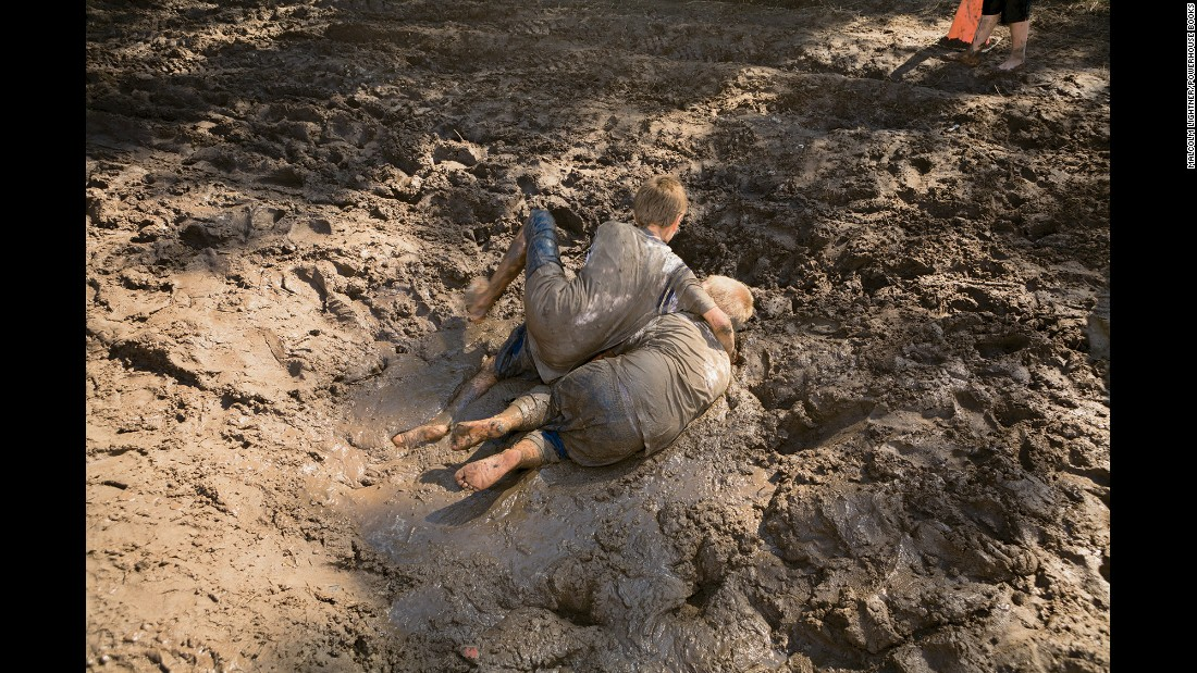 Children wrestle in the mud.
