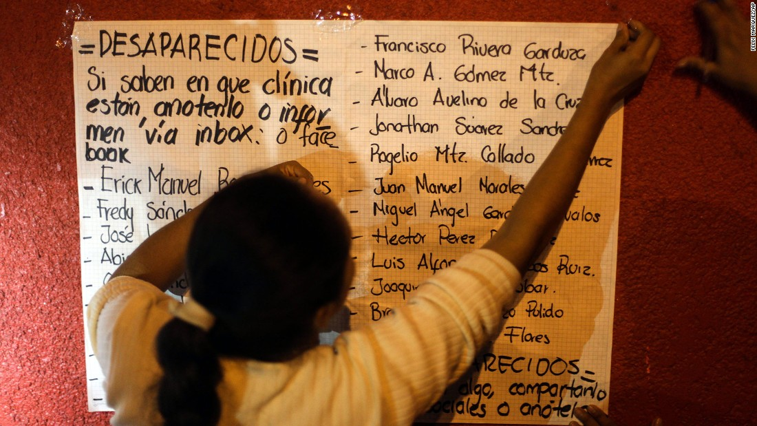 A woman places a list of missing workers outside the hospital.