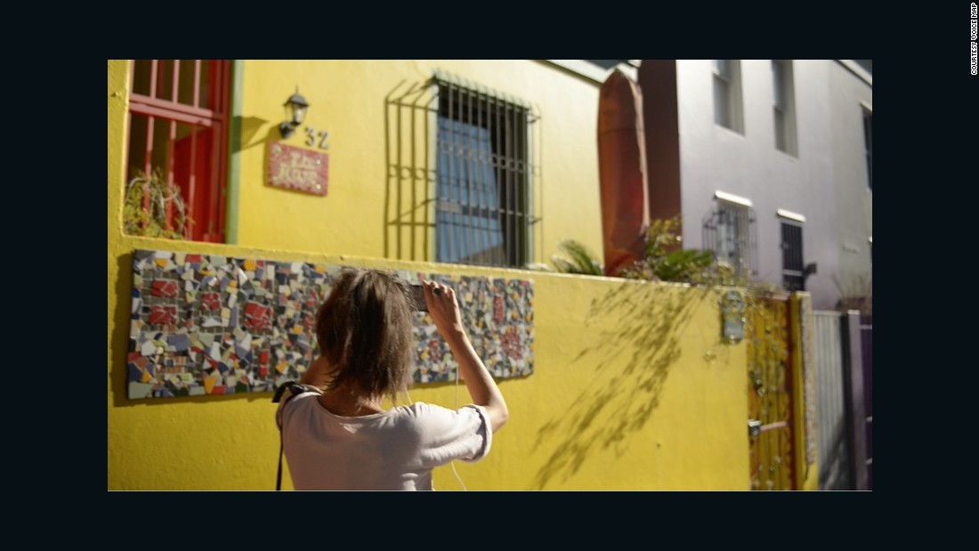 A woman takes an audio tour around Bo-Kaap, guided by a local via VoiceMap.